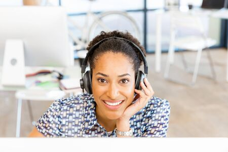 afroamerican: Portrait of smiling afro-american office worker sitting in offfice with headphones