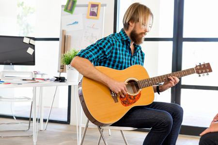Man playing guitar in office 版權商用圖片