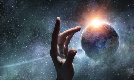 Female hand touching Earth symbolizing faith and religion. Elements of this iamge are furnished by NASA Banco de Imagens