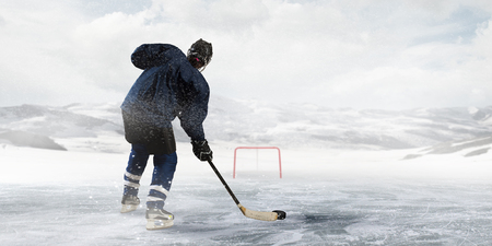 frozen lake: Hockey player on the ice Stock Photo