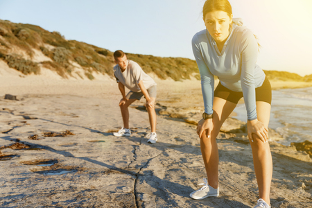 Young couple on beach training together