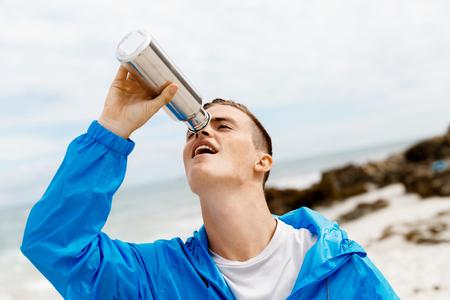L'homme boit dans une bouteille de sport Banque d'images - 82557818