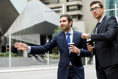 Dos jóvenes empresarios gritando por un taxi Foto de archivo - 82558558