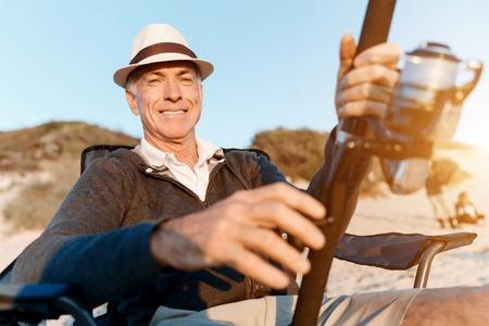 Senior man fishing at sea side photo