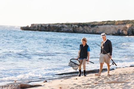 Senior man fishing with his grandson photo