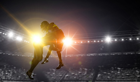 Silhouettes of american football players at arena . Mixed media Banco de Imagens
