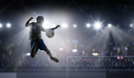 Silhouette of soccer player jumping and kicking ball at stadium . Mixed media Stok Fotoğraf
