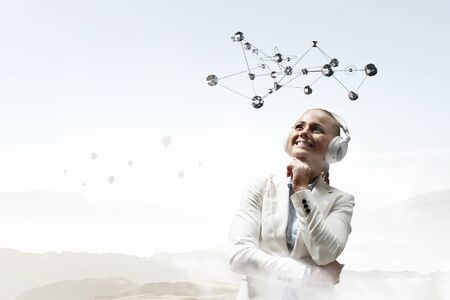 Young blond businesswoman listening music with wireless headphones. Mixed media Stock Photo