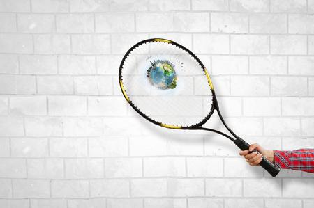 Close of hand holding tennis rocket. Mixed media Stock Photo