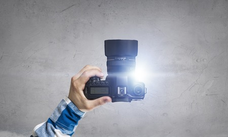 Male hands holding photo camera on the dark wall background Stok Fotoğraf - 82570757