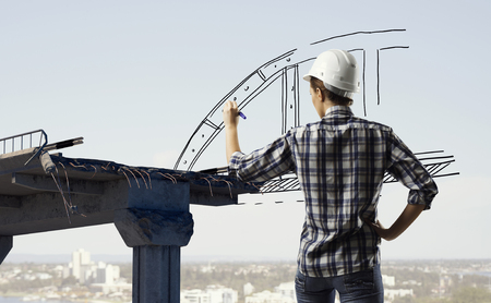 Builder woman taking measures. Mixed media Stock Photo