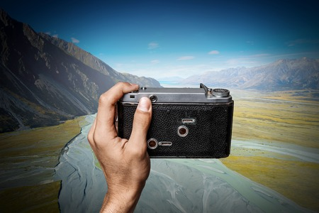 Photographer holding retro camera and taking photos of natural landscape
