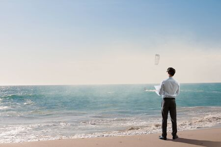Businessman standing on ocean coast and enjoying the view. Mixed media