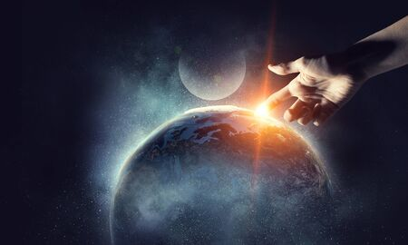 Mans hand touching the Earth planet with finger. 版權商用圖片