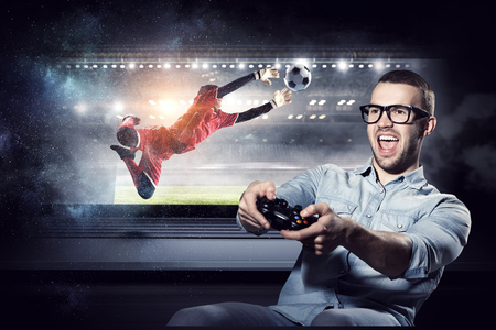 Emotional guy wearing glasses playing gamepad. Mixed media