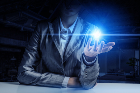 Young businesswoman presenting glass glowing light spot in her hand. Mixed media