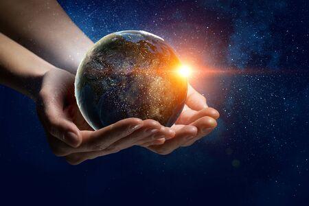 男性の手が地球惑星を保持しています。