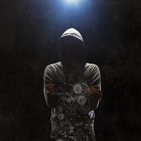 어두운 배경에 대해 hoody를 입고 범죄 남자입니다. 혼합 매체