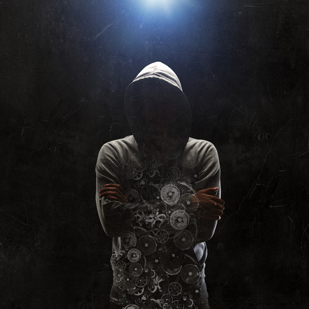 Criminal man wearing hoody against dark background. Mixed media Stock Photo
