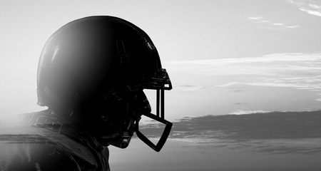 Silhouette of american football player on gray sky background. Mixed media
