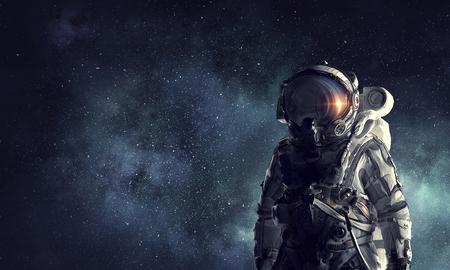 Astronaut against dark night sky background. Mixed media Stock Photo