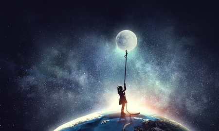 Kid girl catching moon 스톡 콘텐츠