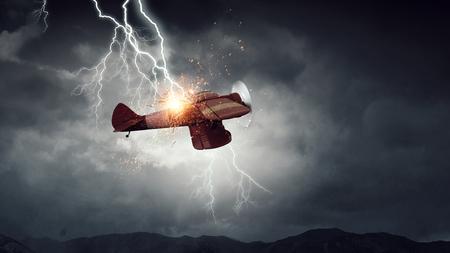暗い空でレトロな飛行機の雷。ミクスト メディア