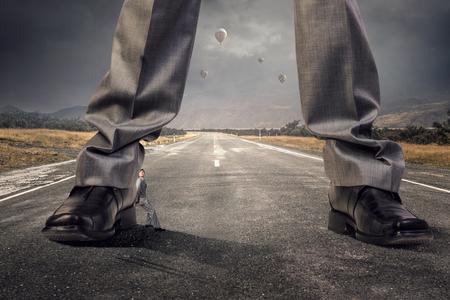 Voeten van reuzezakenman op asfaltweg als machtsconcept. Gemengde media