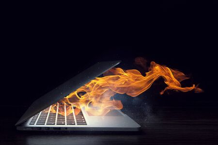 Laptop in fire flames on dark background. Mixed media Banco de Imagens