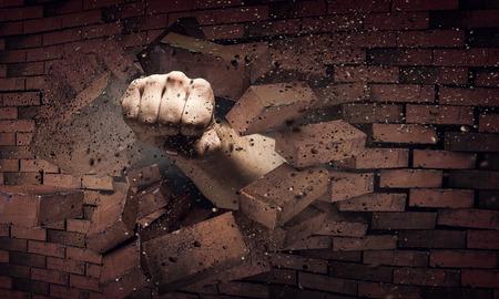 男性の手が拳のレンガの壁を破壊します。ミクスト メディア 写真素材