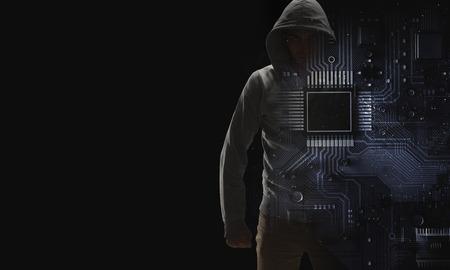 Criminal man wearing hoody against dark background. Mixed media Banco de Imagens