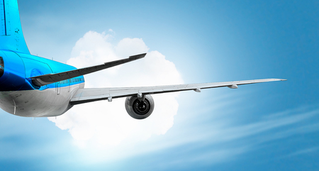 mixed media: Wing of an airplane in blue cloudy sky. Mixed media Stock Photo
