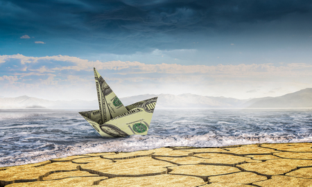 Ship made of dollar banknote in sand desert. Mixed media