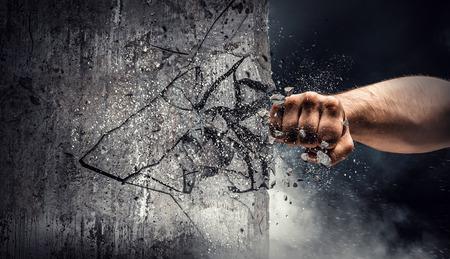 Hand die door de muur breekt. Gemengde media