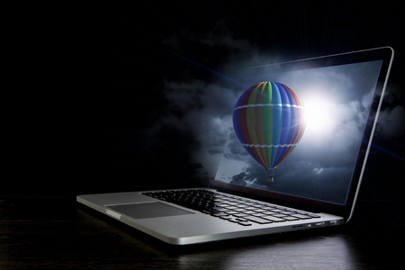 Color aerostat on laptop screen. Mixed media Фото со стока
