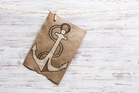 ship anchor: Paper pinned to rope. Mixed media Stock Photo
