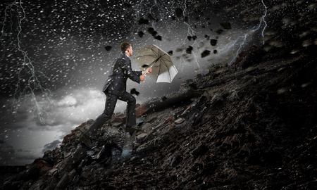 Businessman with black umbrella. Mixed media Stock Photo