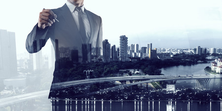 Double exposure of businessman draw on screen and modern city landscape. Mixed media