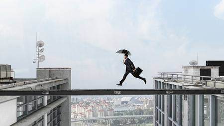 Fearless businessman overcoming difficulty. Mixed media . Mixed media Stock Photo