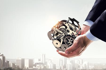 Cogwheel mechanism in hand. Mixed media . Mixed media