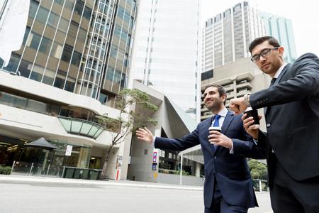 Dos jóvenes empresarios gritando por un taxi Foto de archivo - 85353280