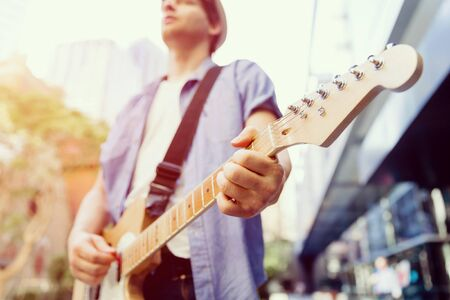 Young musician with guitar in city Stock Photo