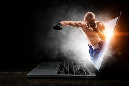 Mannboxer, der Laptop-Bildschirm herauskommt. Gemischte Medien Standard-Bild