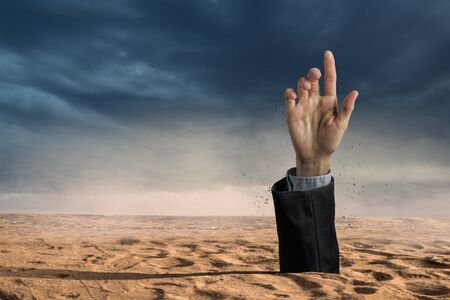 Hand coming out of ground as concept for never give up