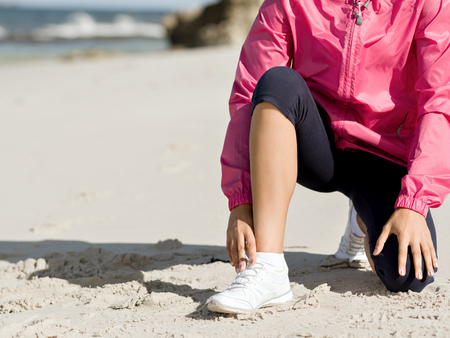 Woman runner tying shoelace at the seaside Stock Photo - 85759899