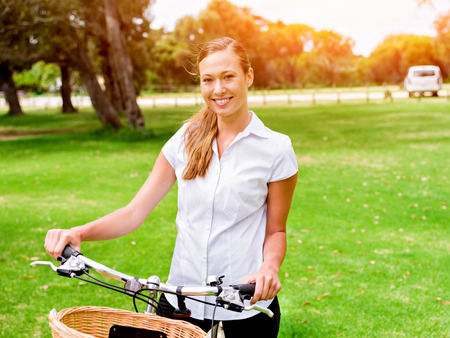 Beautiful young blonde woman with bike in park Reklamní fotografie