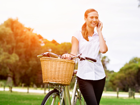 Beautiful young blonde woman with bike in park Banco de Imagens