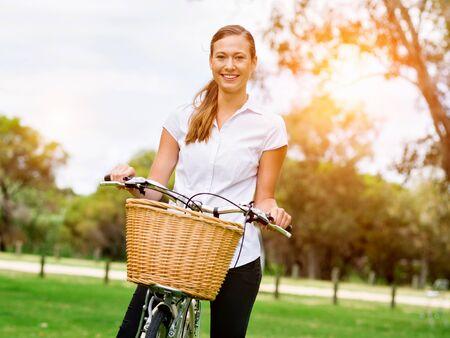 公園での自転車と美しい若いブロンドの女性 写真素材
