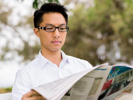 Zakenman die een krant in het park leest Stockfoto - 85810541
