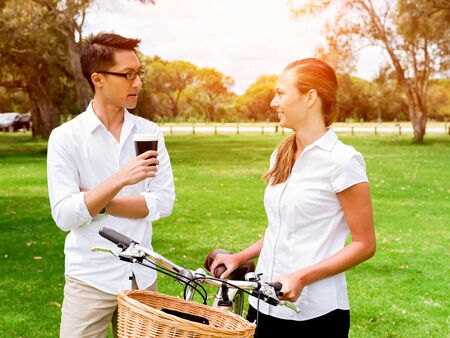 Portrait of smiling couple standing in park with bike talking